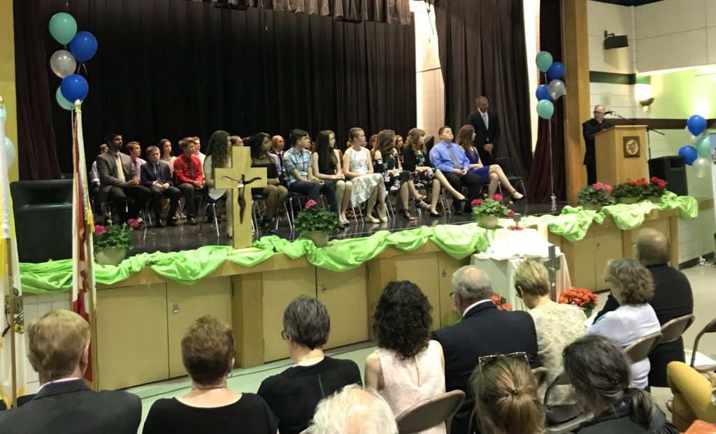 group of students sitting on stage during ceremony