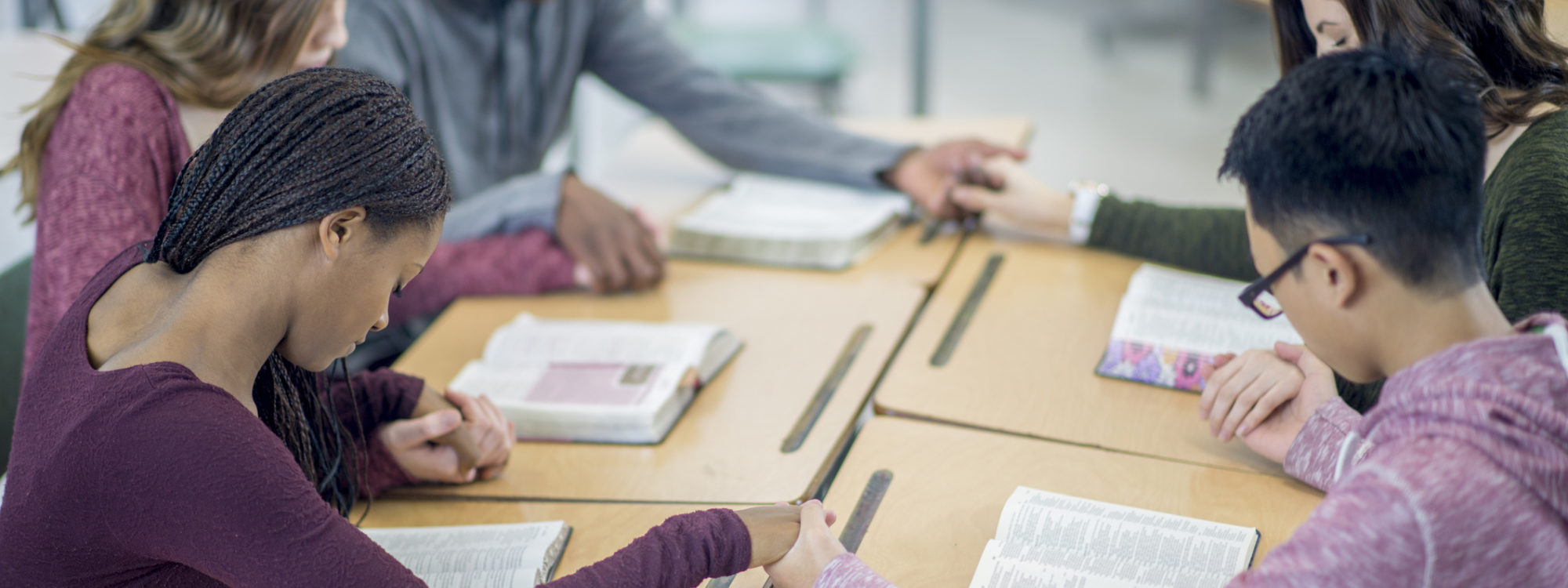 A multi-ethnic group of high school age students are sitting together at their desks and are holding hands while praying together.