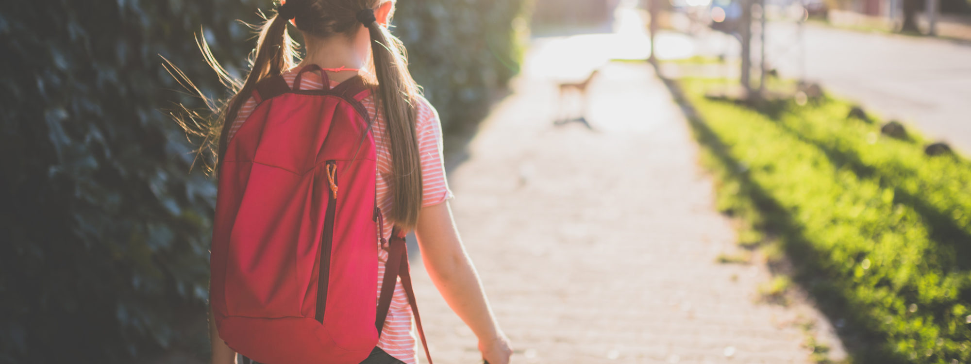 Girls wearing red backpack walking to school