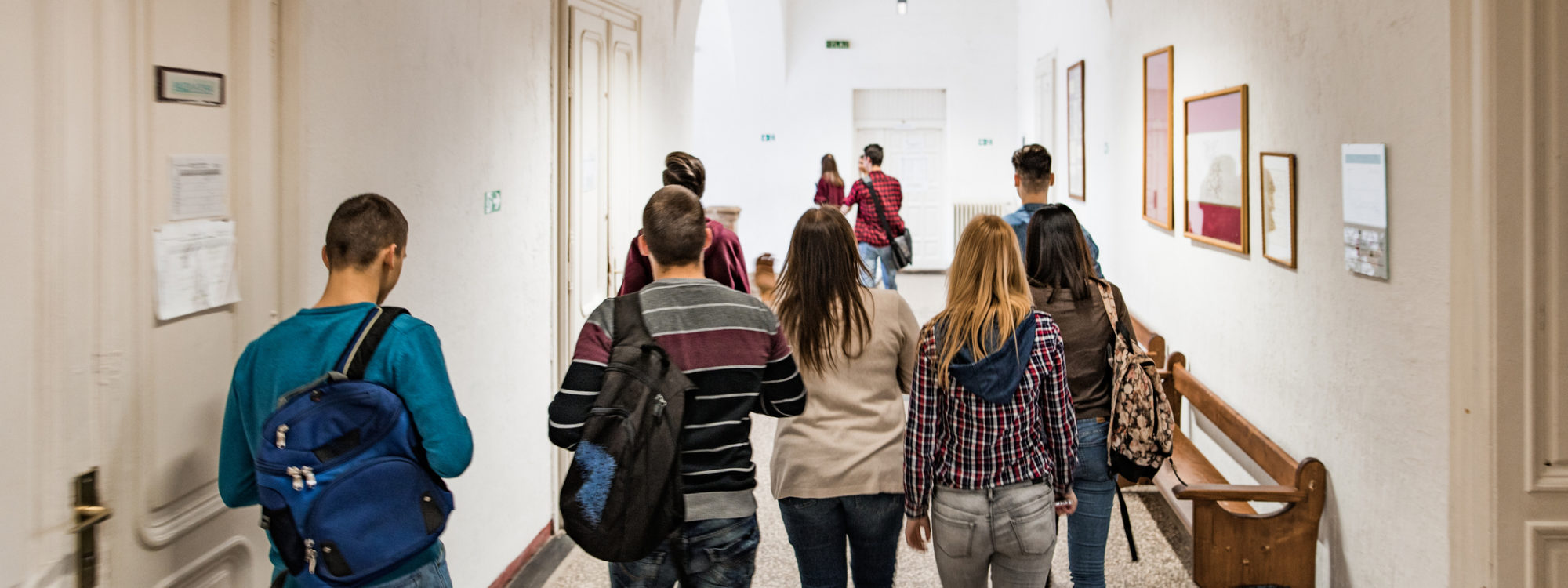 Rear view of high school students walking in the school hallway.