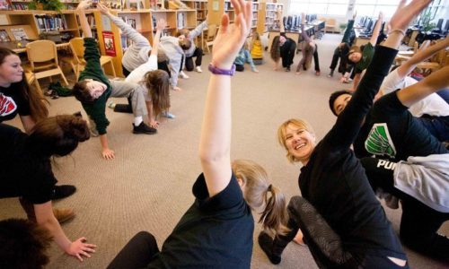 students performing yoga in library
