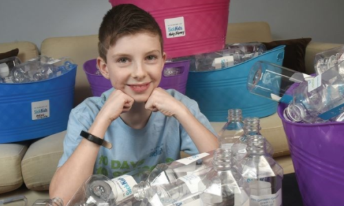 student with plastic water bottles for recycling
