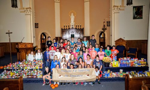 students standing with school food drive collection