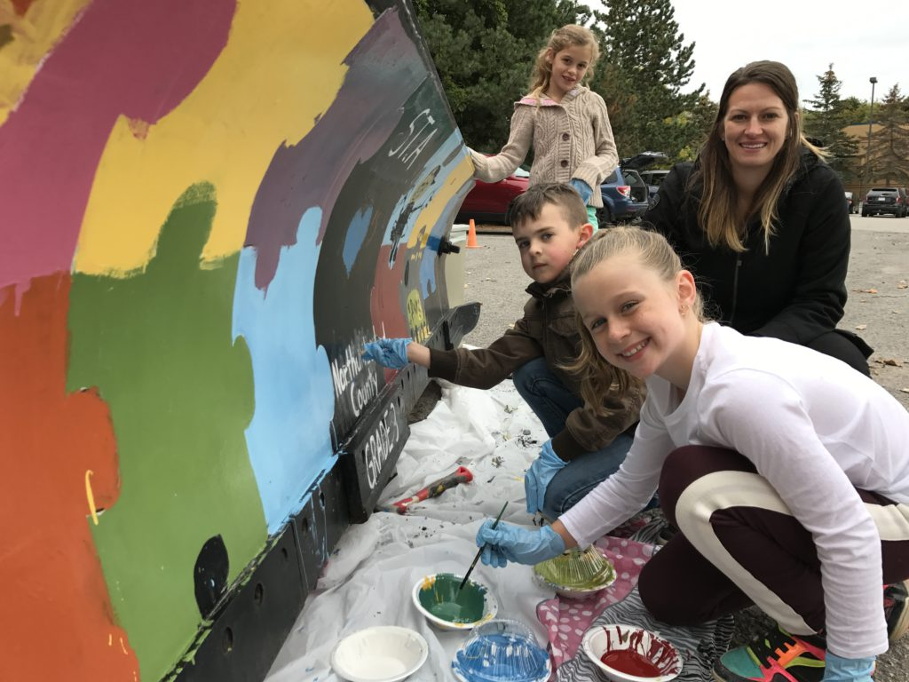 students painting snowplow blade