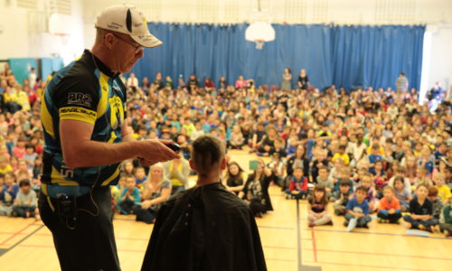 student getting hair cut on stage