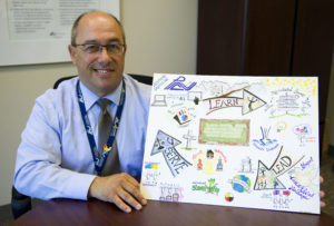 Director holding artwork from a staff member