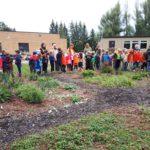 students and staff standing around the school garden