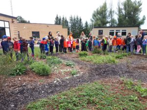 students and staff standing around the school garden