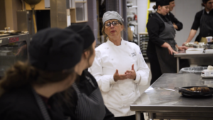 woman instructing students in learning kitchen