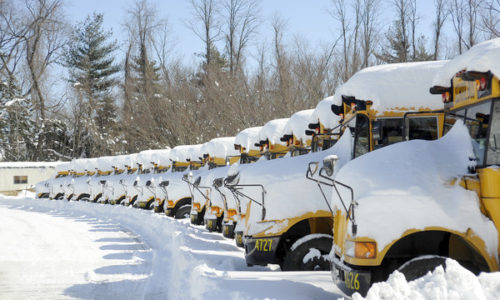 a line of parked busses covered in snow