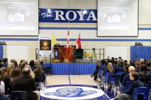 man speaking at podium in gymnasium