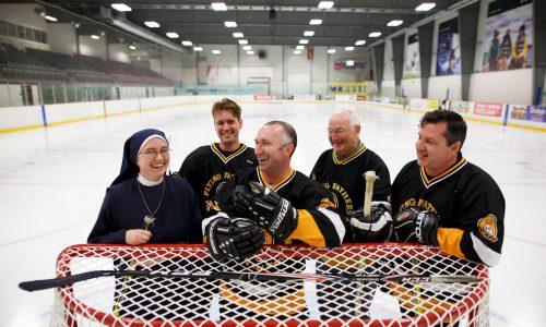 people standing at hockey net