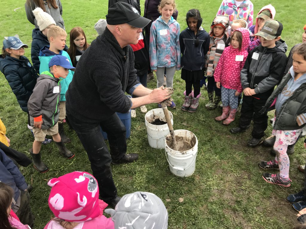 man holding mud in hands surrounded by students