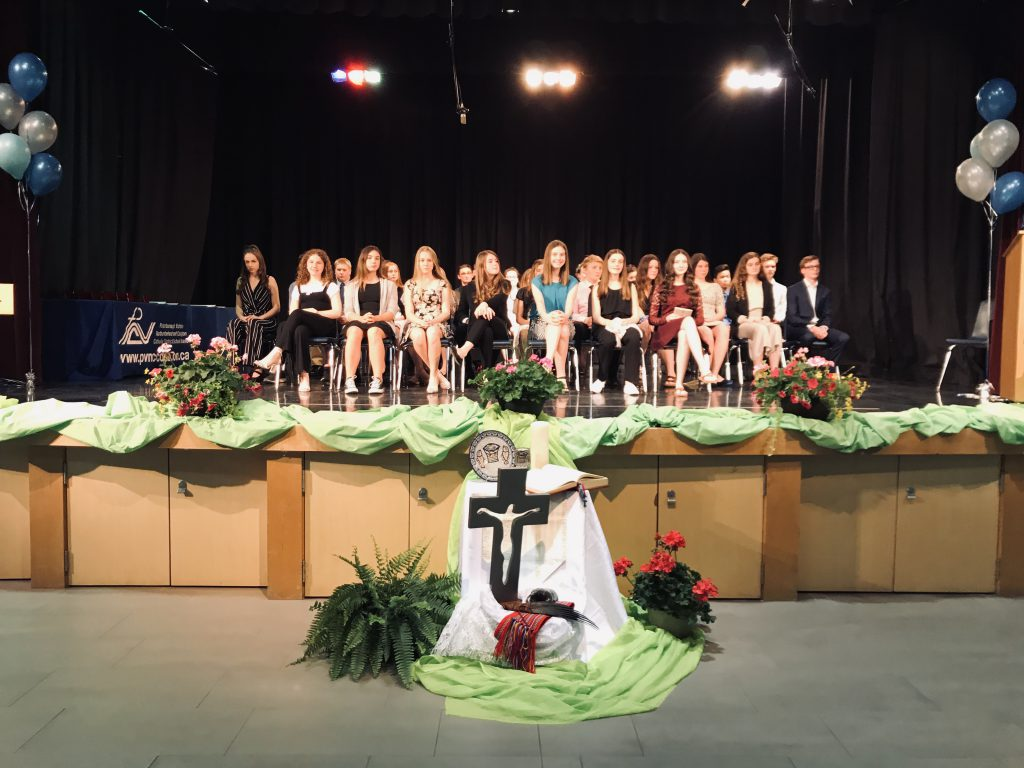 students sitting in chairs on stage