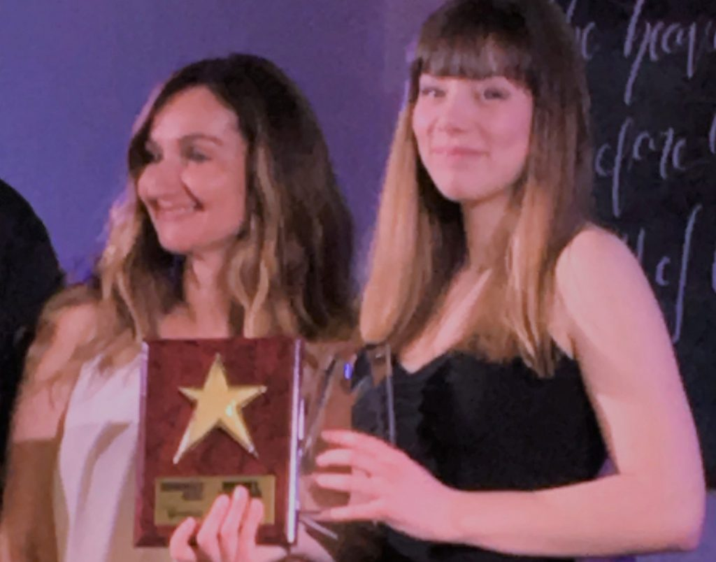student holding awards