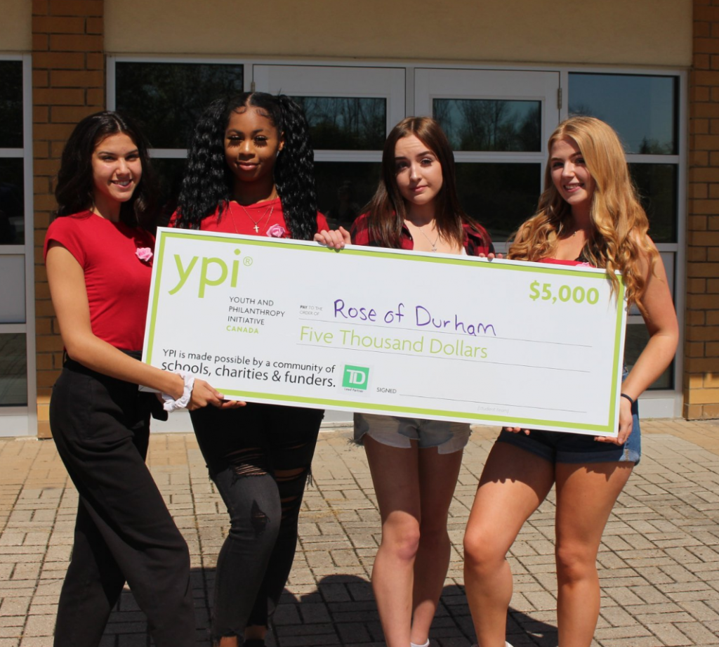 students holding decorative cheque