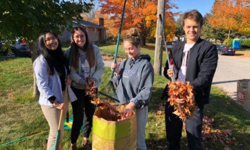 4 students raking up leaves