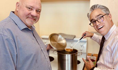 two men serving soup
