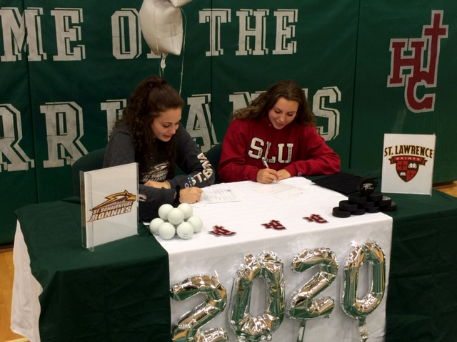 two students sitting at decorated table signing letter