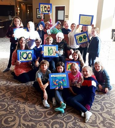 student group holding 100th birthday cards