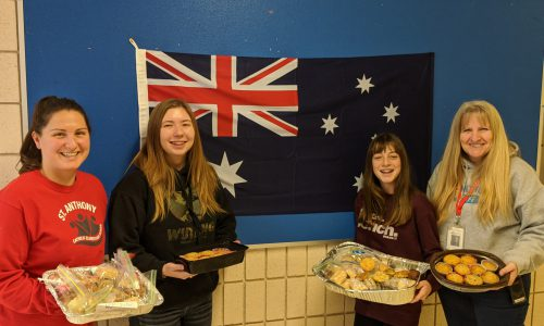 staff and student holding baked goods for sale