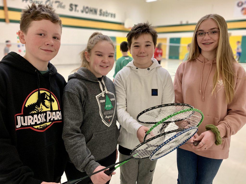 4 students holding badminton rackets