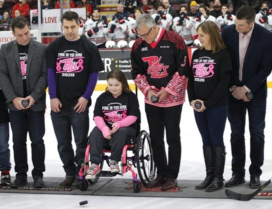 girl in wheelchair performs puck drop for Pink in the Rink