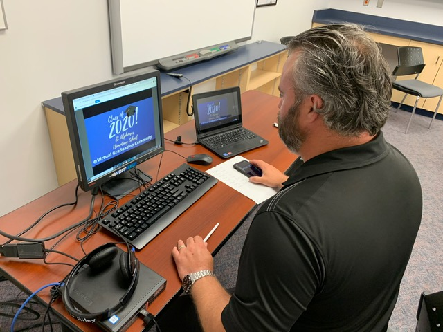 Principal working on a laptop live streams the Board's first ever virtual grad ceremony