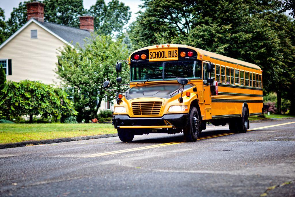Yellow school bus driving along street