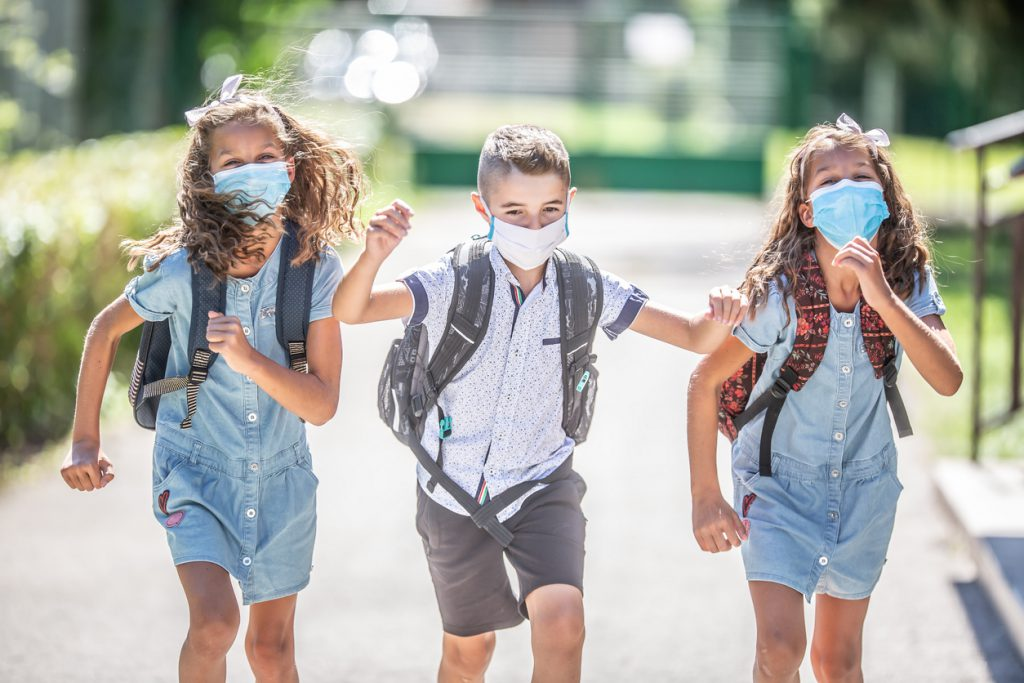 Happy schoolchildren with face masks run from the joy of returning to school